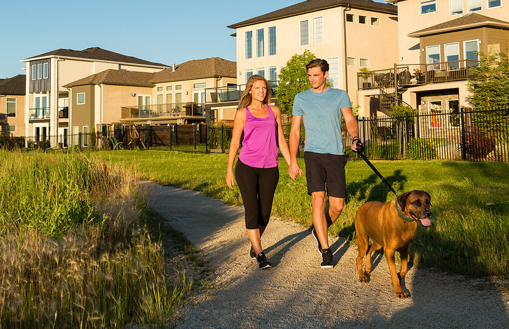 Couple walking on trail with dog